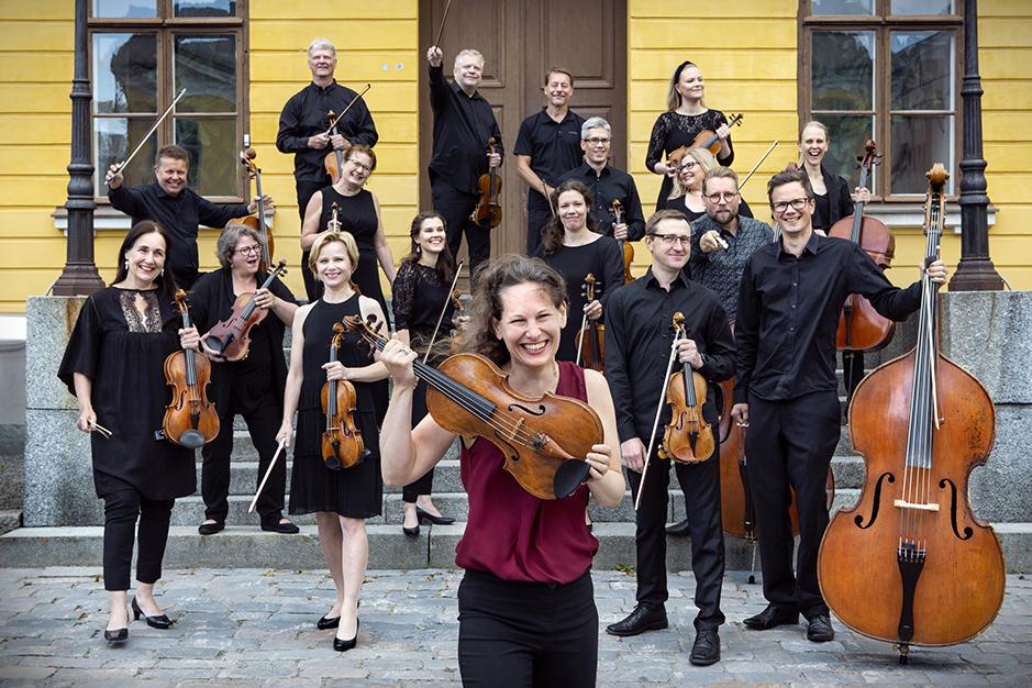 Keski-Pohjanmaan Kamariorkesterin soittajia seisoo talon edessä soittimien kanssa.
